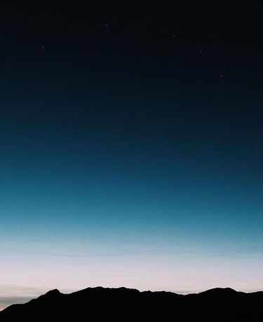 Foto di un cielo progressivamente illuminato dalla luce del sole, il cui colore passa dal rosa al blu zaffiro, sopra una catena di montagne ancora nere.